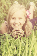 Carefree  smiling blonde girl on sunny grass