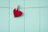 Valentine's day. A red heart hanging on a clothesline. - 76927347