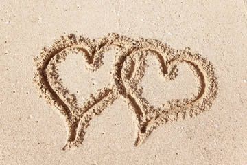 Hearts drawn on the beach sand.