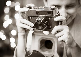 Smiling woman photographed retro camera.