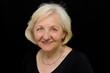 canvas print picture - Lächelnde Seniorin vor schwarzem Hintergrund