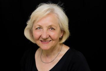 Lächelnde Seniorin vor schwarzem Hintergrund