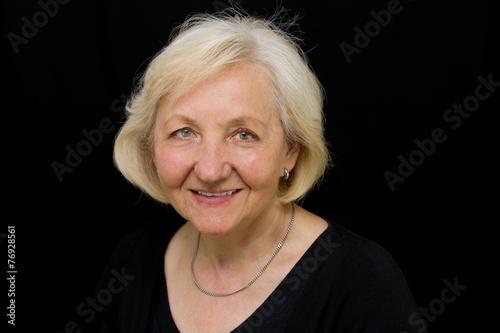 canvas print picture Lächelnde Seniorin vor schwarzem Hintergrund