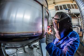 Man welding with reflection of sparks on visor. Hard job.