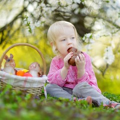 Adorable toddler girl eating chocolate bunny