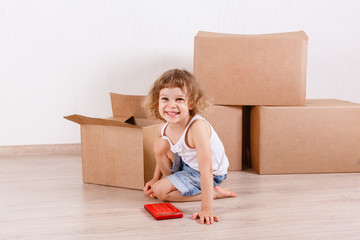 Child sits in a room near the boxes.