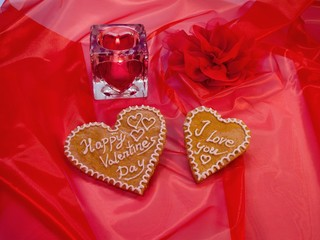 Saint Valentine's hearts from gingerbread on taffeta with candle