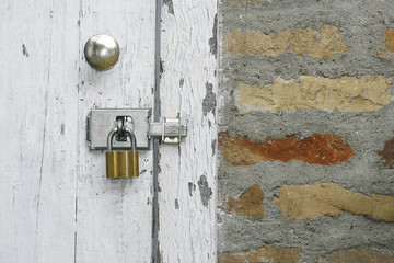 Old wooden rustic door with metal padlock