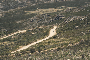 Motorcycle driving on dirt road in Swartberg mountain landscape.