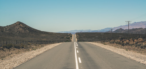 Endless road with blue sky in Swartberg semi desert landscape. W