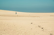 canvas print picture - Bright sand dunes with female tourist walking to the horizon. Cl