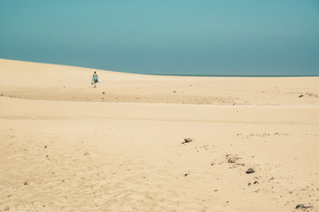 Bright sand dunes with female tourist walking to the horizon. Cl