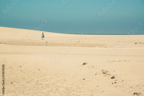 canvas print picture Bright sand dunes with female tourist walking to the horizon. Cl