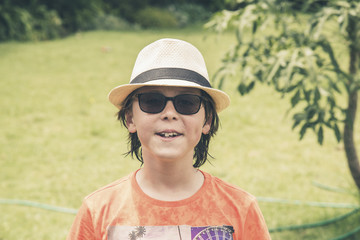 Teenage summer boy with hat and sunglasses in garden.
