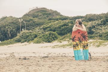 Teenage boy with blonde hair on the beach with bodyboard. Gonubi