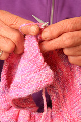 Close up of senior lady hands knitting.