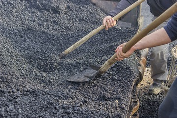 Asphalt workers with a shovel filling wheelbarrow with asphalt 3