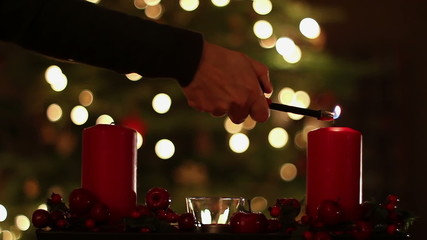 Female hand lighting a candle. Christmas tree in the background