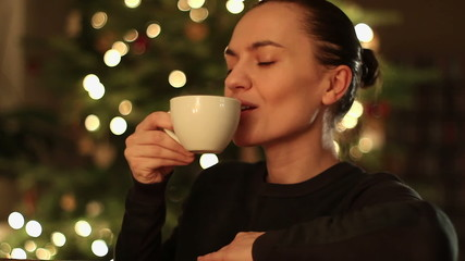 Happy young woman with coffee in front of Christmas tree