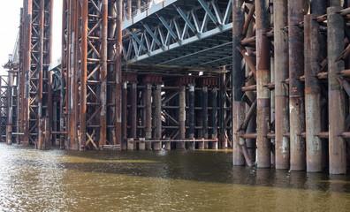 Bridge construction. Rusty metal piers.