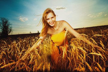 Pretty girl is walking on the wheat field on the sunset backgrou