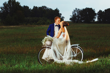 Kissing couple near the bicycle on the fields background