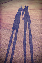 Vintage stylized picture of couple's shadow on beach.