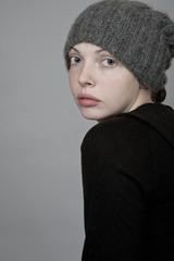 Девушка в вязанной шапке оглядывающийся назад (студийная съемка)