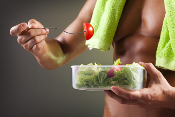 Strong man holding a bowl of fresh salad on dark background