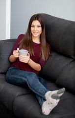 Young girl lying on the sofa drinking tea