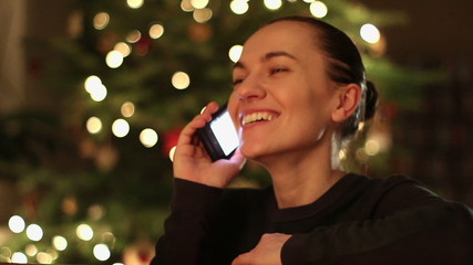 Woman talking cell phone in front of christmas tree