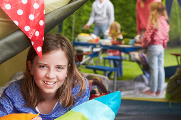 Girl Enjoying Family Camping Holiday On Campsite