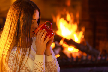Girl warming up at fireplace holds mug