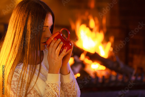 canvas print picture Girl warming up at fireplace holds mug