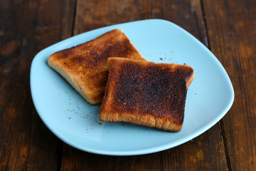 Burnt toast bread on turquoise plate, on wooden table