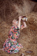Attractive girl in the hay. Drinking milk