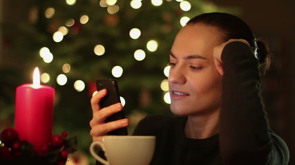 Surprised young woman reading sms near christmas tree