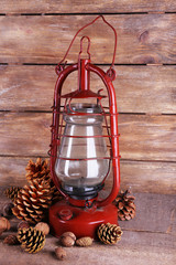 Kerosene lamp with cones ans walnuts on wooden planks