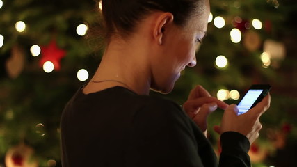 Young woman writing sms in front of Christmas tree