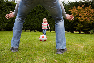 Father And Daughter Playing Football In Garden Together