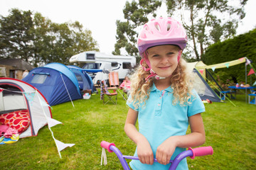 Girl Riding Scooter Whilst On Family Camping Holiday