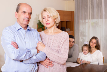 Sad mature couple and young parents with child