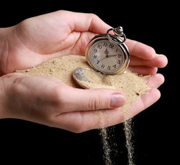 Silver pocket clock in hands and sand flowing away