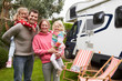 Portrait Of Family Enjoying Camping Holiday In Camper Van - 76946756