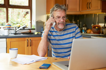 Mature Man Using Mobile Phone Looking At Home Finances