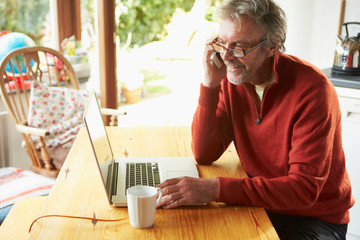 Mature Man Using Mobile Phone And Laptop