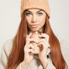 Redhead teenage girl with beige knit beanie and coffee