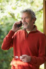 Mature Man Using Cordless Phone At Home