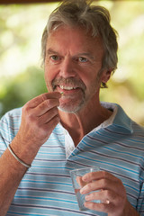 Mature Man At Home Taking Tablet