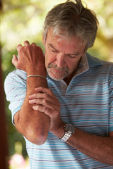 Mature Man Suffering From Painful Elbow At Home